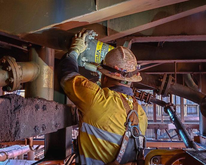 A worker fitting a flexible Slurryflex hose spool in a processing plant